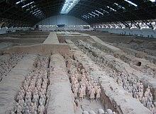 Photographie des soldats de l'armée en terre cuite dans une fosse couverte d'un hangar immense.
