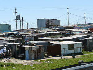 Shanty town - A shanty town near Cape Town, South Africa. These slums were built by the apartheid era government to segregate people by color and ethnic origin. The above Khayelitsha Township is Africa's largest, with shanty homes served with disorganized electrical lines, with one shed showing a car parked inside.