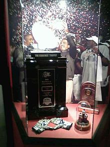 Coaches' Trophy and championship rings in a displaycase.