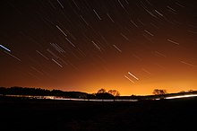 Short streaks of light on a dark sky, showing star trails that were photographed with a long exposure.