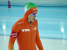 Ireen Wüst se préparant à prendre le départ d'une course. Elle porte une combinaison à capuche et des lunettes de protection.