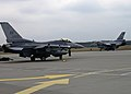 A Polish F-16 Fighting Falcon aircraft, right, taxis past a U.S. Air Force F-16 assigned to the 555th Fighter Squadron at Lask Air Base, Poland, before a training mission March 18, 2014 140318-F-BH566-226.jpg