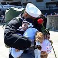 A U.S. Sailor assigned to the aircraft carrier USS John C. Stennis (CVN 74) hugs his wife and daughter on the pier during a homecoming ceremony at Naval Station Kitsap in Bremerton, Wash., May 3, 2013 130503-N-KD696-215.jpg
