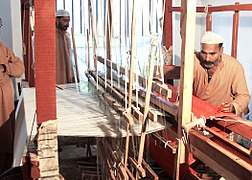 A convicted prisoner trained as a weaver during confinement in Central Jail Faisalabad, Pakistan weaving a red blanket used in Jail Hospitals on a traditional manual loom in 2010.jpg