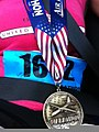 A marathon medal hangs around the neck of U.S. Air Force Senior Airman Naomi Griego after participating in the Air Force Marathon at Wright Patterson Air Force Base, Ohio, Sept 130921-F-PD986-001.jpg
