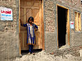 A young girl stands outside a house undergoing flood-proofing work in Sindh, Pakistan, April 2012 (8406169194).jpg