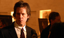 Kevin Bacon en costume fait face au photographe.
