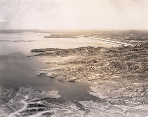 Fort Peck Dam - An aerial view of the main Fort Peck Dam structure looking westward with Milk Coulee Bay in the foreground. Just out of view to right would be the intake for the spillway. June 29, 1938. Courtesy, estate of Robert A. Midthun.