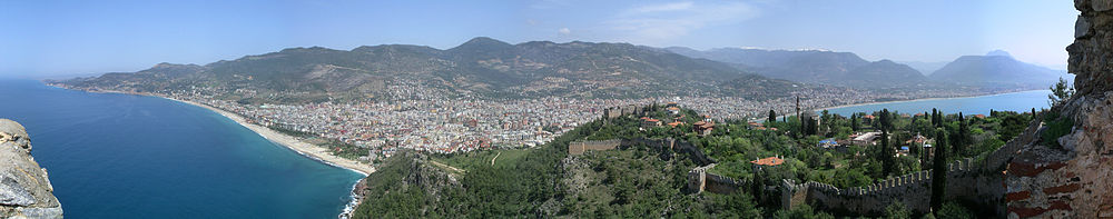 A panoramic view of a city beneath a mountain range with blue sea on both sides of a peninsula. On the peninsula is a castle wall and red roofed buildings. A young girl peers into the scene over the wall on the far left.