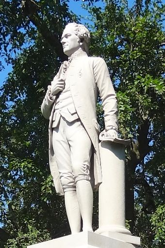Statue view showing left hand, document, and column