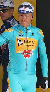 A man wearing a blue and yellow cycling jersey while standing.