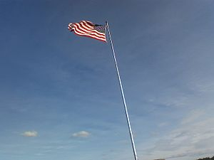 A US flag flying on a tall pole.