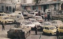 photo d'un blindé accompagné de militaires en armes surveillant un embouteillage.