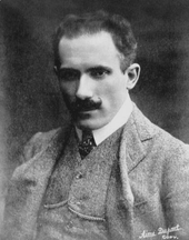 A head-and-shoulders photograph of a man in a three-piece suit with tie and watch-chain. His intense-looking appearance is complemented by receding dark curly hair and a curled moustache.