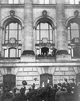 Scheidemann proclama la repubblica dal balcone ovest (seconda finestra a nord del portico) del palazzo del Reichstag.