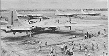 Four 4-engined World War II-era aircraft sitting on the ground at an airstrip. Groups of people are working near each aircraft.