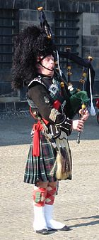 A piper playing the Great Highland Bagpipe.