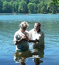 A baptism in a river. Two men are standing hip-deep in blue water with trees in the background.
