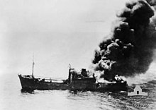 A ship burning from the stern settles in the water.