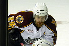 A Caucasian ice hockey player bent over at the waist. He wears a white helmet and has a large beard.