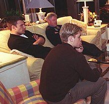 Bill Clinton, Ben Affleck and Matt Damon sit on two sofas while looking towards a television screen