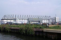 Внешний вид футбольного стадиона ассоциации Carrow Road.  На переднем плане река.