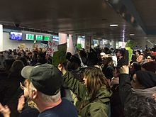 Crowd of protesters inside O'Hare International Airport, some holding signs.