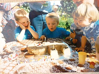 Australian Women's Weekly Children's Birthday Cake Book - Child blowing out candle on the brown bear cake (1986)