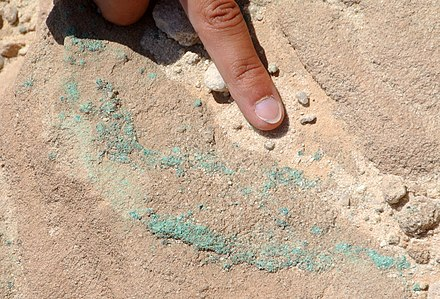 Copper ore (chrysocolla) in Cambrian sandstone from Chalcolithic mines in the Timna Valley, southern Israel. Chrysocolla Timna 070613.jpg