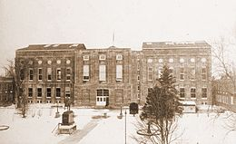 A sepia-toned photograph of a large, rectangular building.