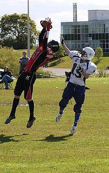 Zwei Fußballspieler, ein offensiver Empfänger und ein defensiver Eckball, greifen beide nach einem geworfenen Fußball.  Der Cornerback befindet sich vor dem Empfänger, der Ball ist fast in seinen Händen.