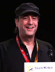 A man wearing a cap smiles as he looks into the distance.