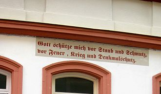 "Deutsche Stiftung Denkmalschutz - ""God save me from dust and dirt, from fire, war, and the Denkmalschutz"" on a building in Bamberg"