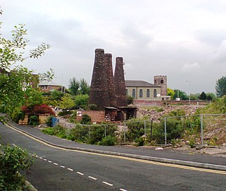 Burslem - Disused Bottle ovens of Acme Marls on Bourne's Bank, Burslem, Stoke-on-Trent, with St. John's Church, Woodbank Street, in the background whose sandstone tower dates from 1536 (Photographed May 2008)