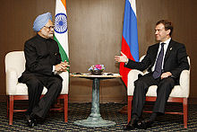 Two seated men converse. The first is dressed in Indian clothing and turban and sits before an Indian flag; the second is in a Western business suit and sits before a Russian flag.
