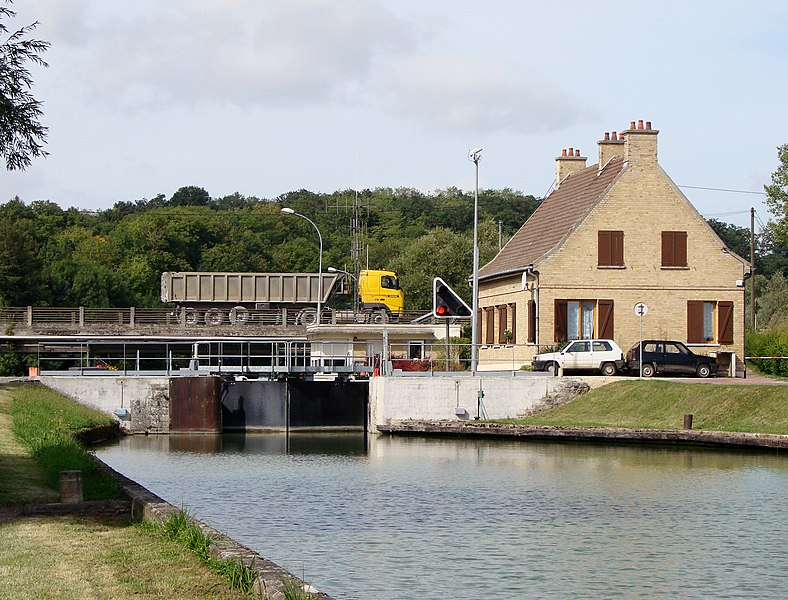 The canal lock on the Canal latéral à l'Aisne in Berry-au-Bac, with the bridge on the background.