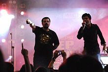 Khan and Ahmed Ali Butt onstage; Khan is singing, and Butt is holding his microphone to the audience
