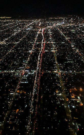 Figueroa Street - Figueroa Street (left), Harbor Freeway (center), and S Broadway (right) night aerial from the south, with downtown Los Angeles in the distance. Figueroa Street turns and become less visible at the University of Southern California.