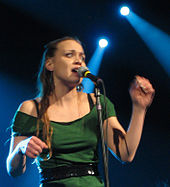 Fiona Apple wearing a green outfit while singing.