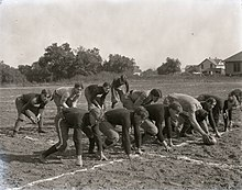 A football team crouching in preparation for a snap on a dirt field