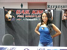 An Asian female with dark hair wearing light-blue wrestling gear standing in front of a crowd.