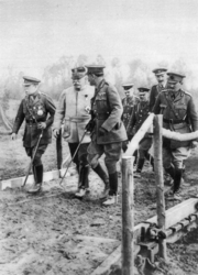 Two British and one French General lading a group of four British officers across a small wooden bridge