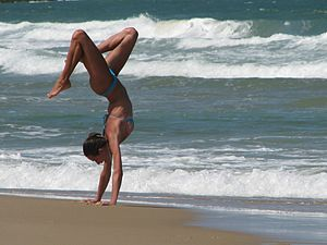English: Woman makes a handstand on the beach,...