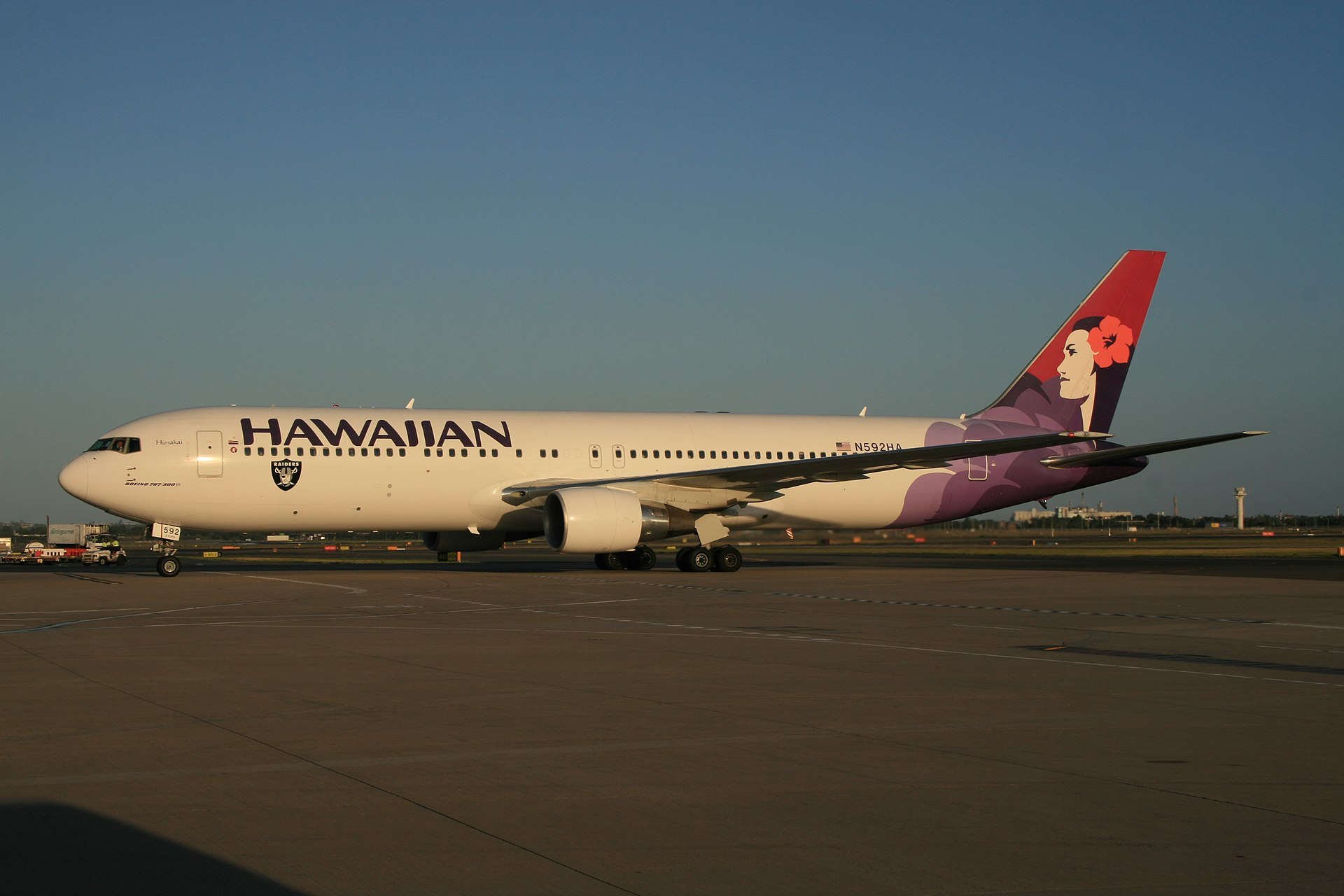 """A white twin-engine plane painted with the word """"HAWAIIAN"""" in the front above the windows, a black, silver, and white logo of a pirate's head on the forward bottom of the fuselage, and a woman in different purple hues on the tail taxis at an airport"""