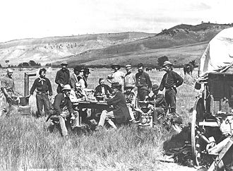 Ferdinand Vandeveer Hayden - A noon meal in Ferdinand V. Hayden's camp of the U.S. Geological and Geophysical Survey. Red Buttes, Wyoming Territory, August 24, 1870. Hayden sits at far end of table in dark jacket. (Photo by William Henry Jackson, standing at far right)
