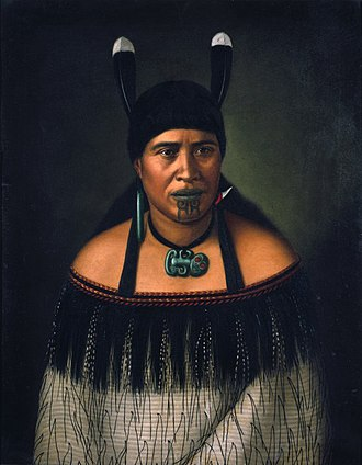 Culture of New Zealand - Hinepare of Ngati Kahungunu, is wearing a traditional korowai cloak adorned with a black fringe border. The two huia feathers in her hair, indicate a chiefly lineage. She also wears a pounamu hei-tiki and earring, as well as a shark tooth (mako) earring. The moko-kauae (chin-tattoo) is often based on one's role in the iwi.