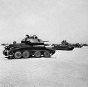 Several tanks parked on sandy-desert surface.