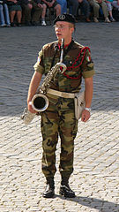 A military band saxophonist holding baritone saxophone