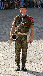 A saxophonist in a military band of the Italian army, playing a baritone saxophone.