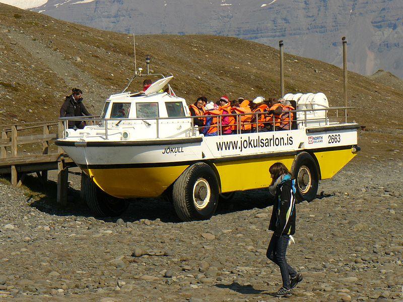 """""""Vehicule jaune et blanc a l'arrêt au sec devant un ponton, avec une vingtaine de personnes a bord portant des gilets de securité, dans un paysage minéral"""""""